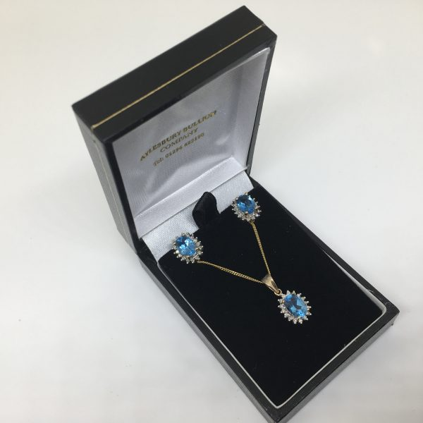 9 carat yellow gold blue topaz and diamond pendant, chain and earring set