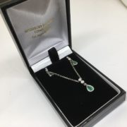 Preowned 9 carat white gold emerald and diamond pendant, chain and earring set